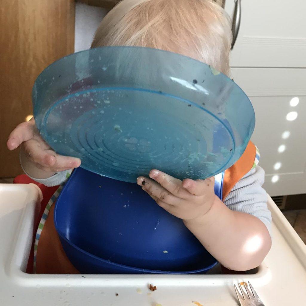 Kleinkind isst am Familientisch