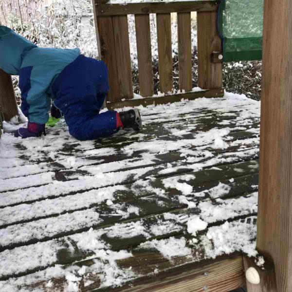 Kind spielt im Schnee