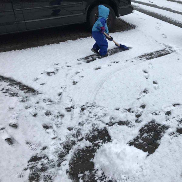 Kind räumt Schnee mit Schneeschaufel