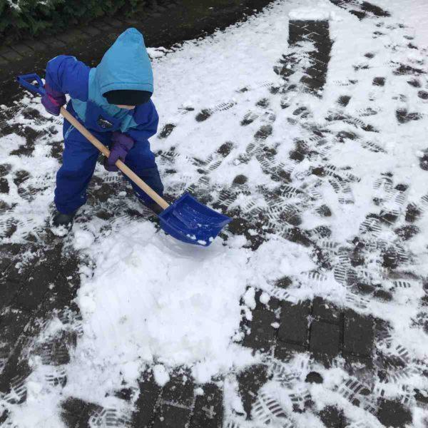 Kind spielt mit Schneeschaufel