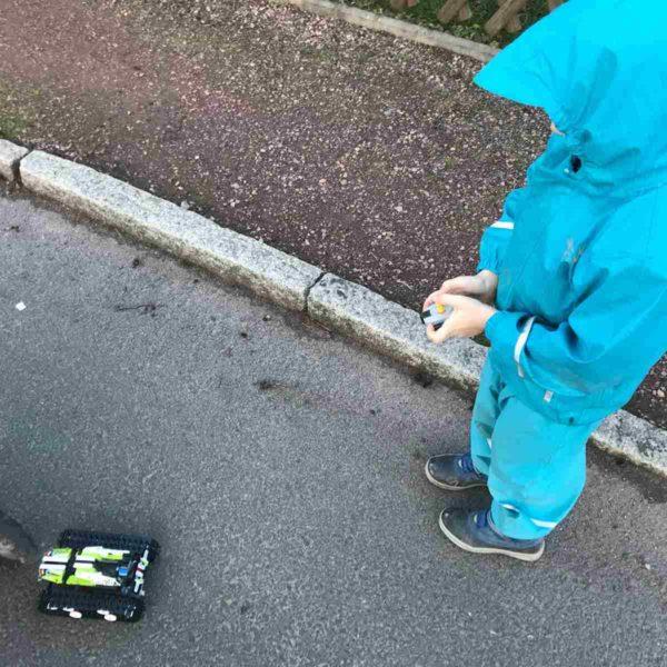 Kind fährt mit ferngesteuertem Lego-Auto