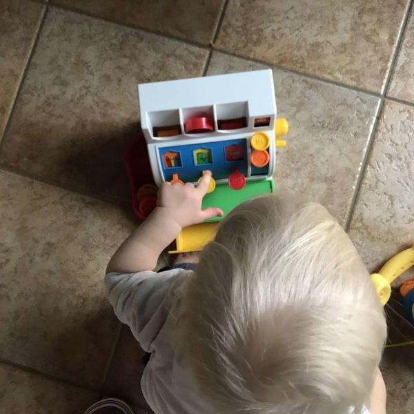 Kleinkind spielt mit Kinderkasse