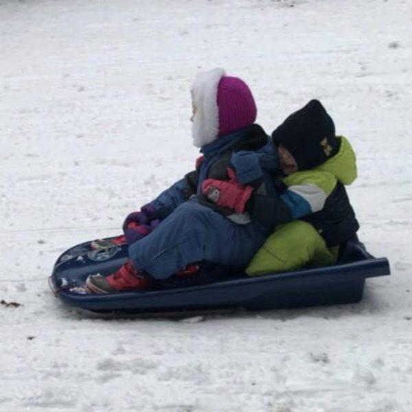 Kinder fahren gemeinsam Schlitten