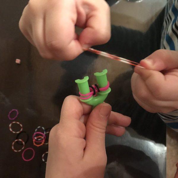 Kinder spielen mit Loombändern