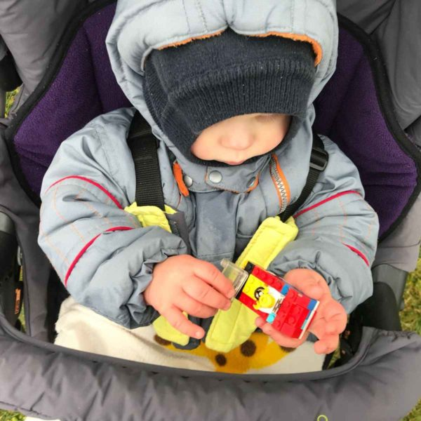 Kleinkind spielt im Kinderwagen