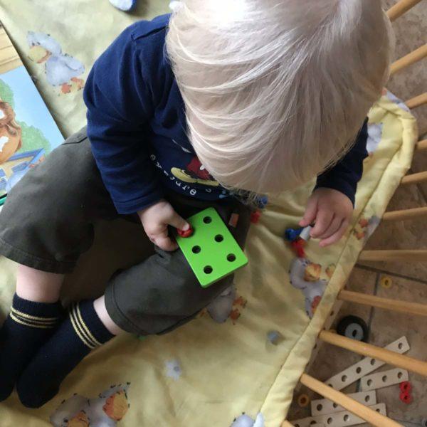 Kleinkind spielt mit Schrauben