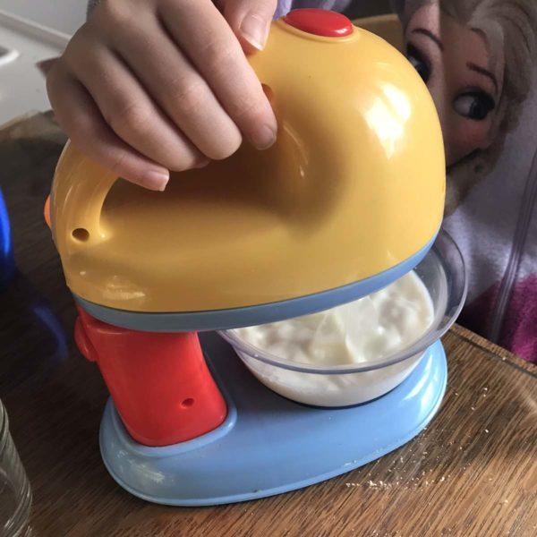 Kind mixt Milch mit dem Kindermixer