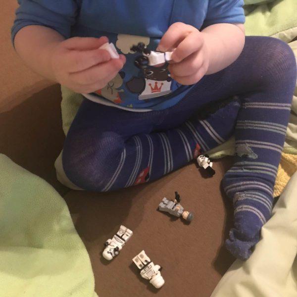 Kleinkind spielt mit Lego-Männchen