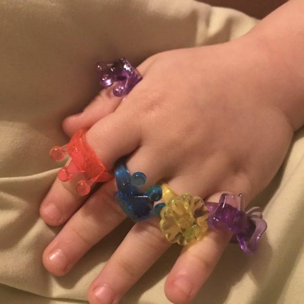 Kind trägt Kinderringe an jedem Finger