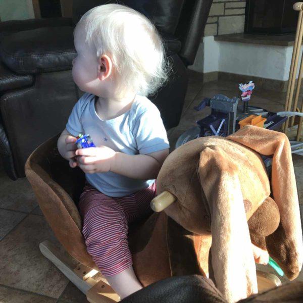 Kind schaukelt auf Schaukelpferd