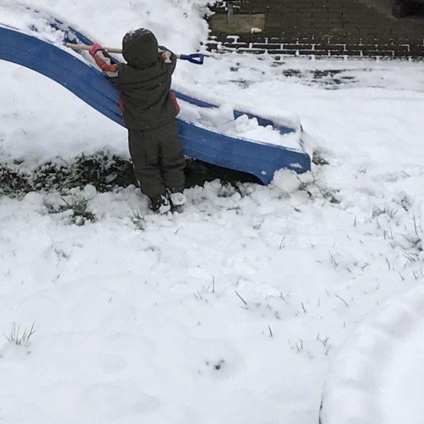 Kind schippt Schnee