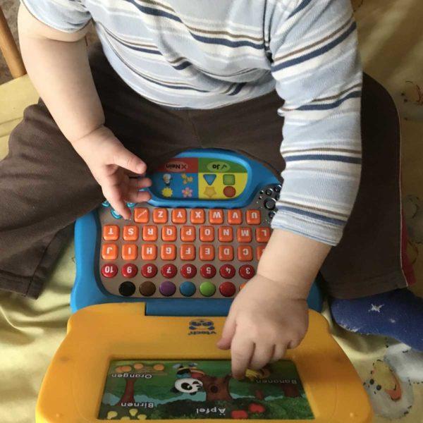 Kind spielt mit Lerncomputer