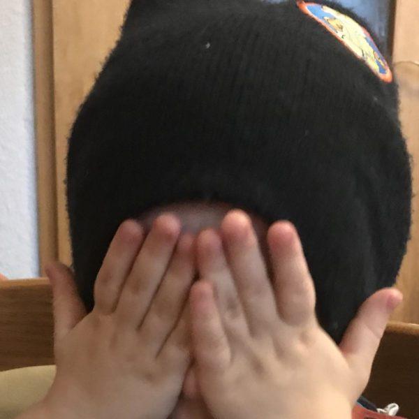 Kleinkind sitzt mit Mütze am Tisch