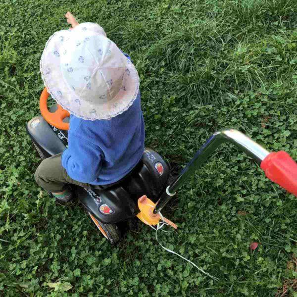 Kind fährt mich Fahrzeug im Garten